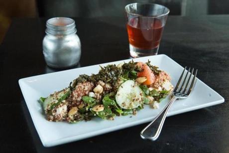 A salad of quinoa with grapefruit, almonds, cucumber, feta, and tea leaves.